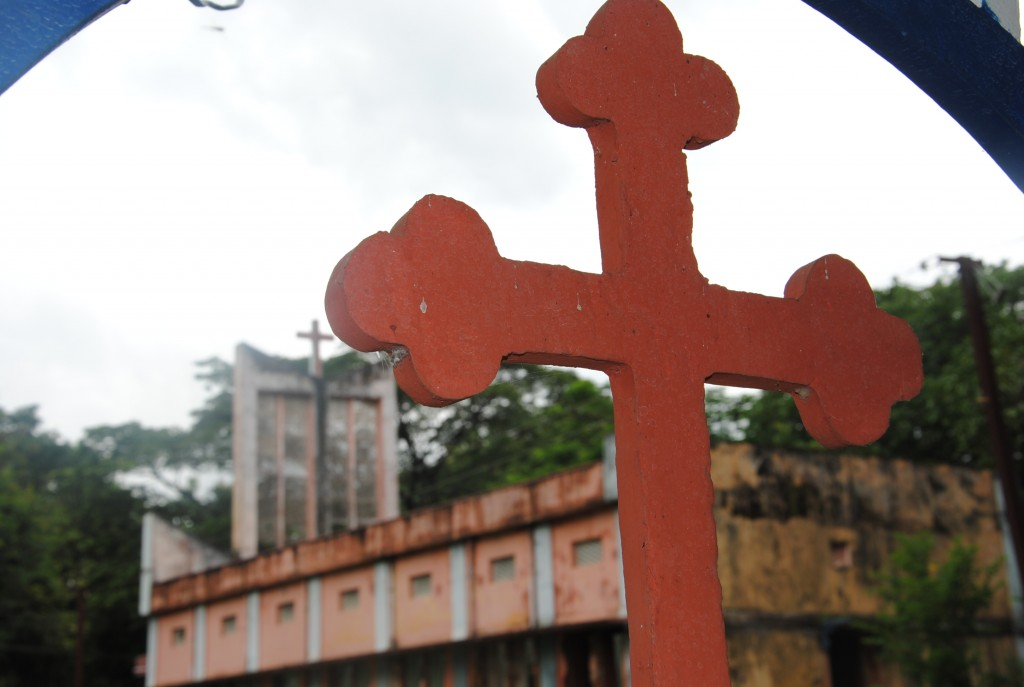 Vandalised parish church of St Teresa of the Child Jesus parish in the backgound, in Muniguda, Orissa