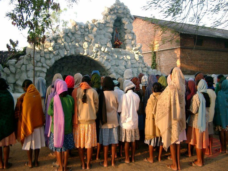 Lourdes gruta en India con gente rezando para web