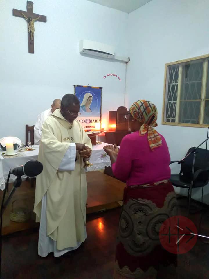 Mozambique sacerdote da la comunion con afiche de radio maria