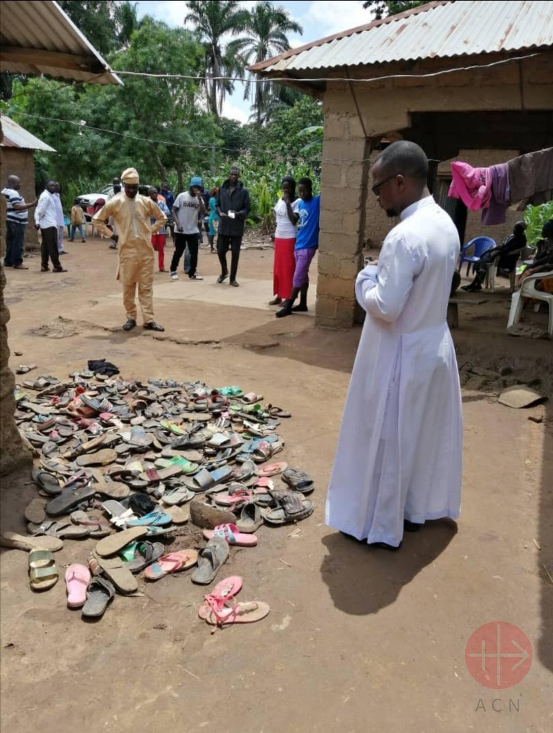 Nigeria padre Sam contempla un montón de sandalias