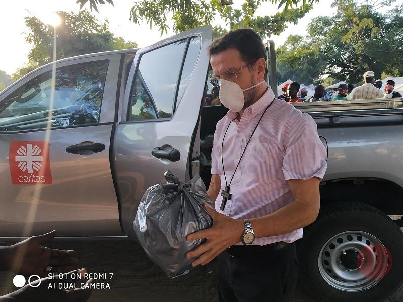 Mozambique monseñor Lisboa con bolsa de alimentos en camioneta caritas web