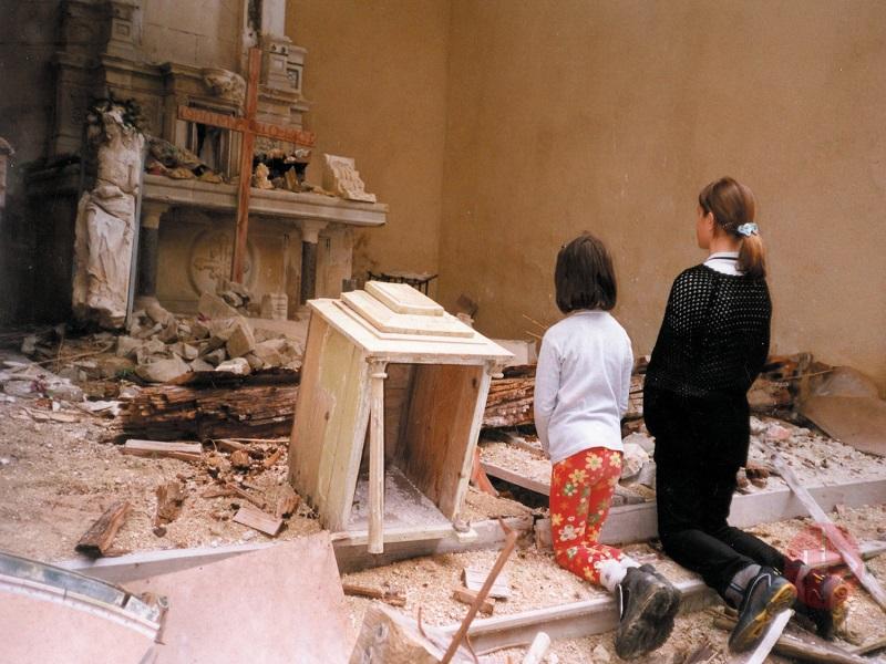 Bosni H niñas rezando frente a altar destruido