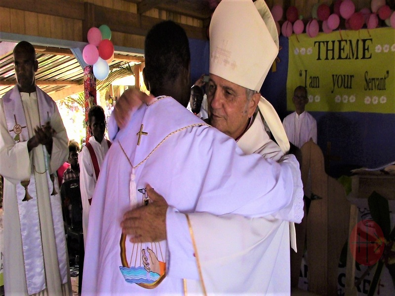 Islas Solomon Bishop Luciano Capelli embracing Fr. Benedict Qelo after his priestly ordination web