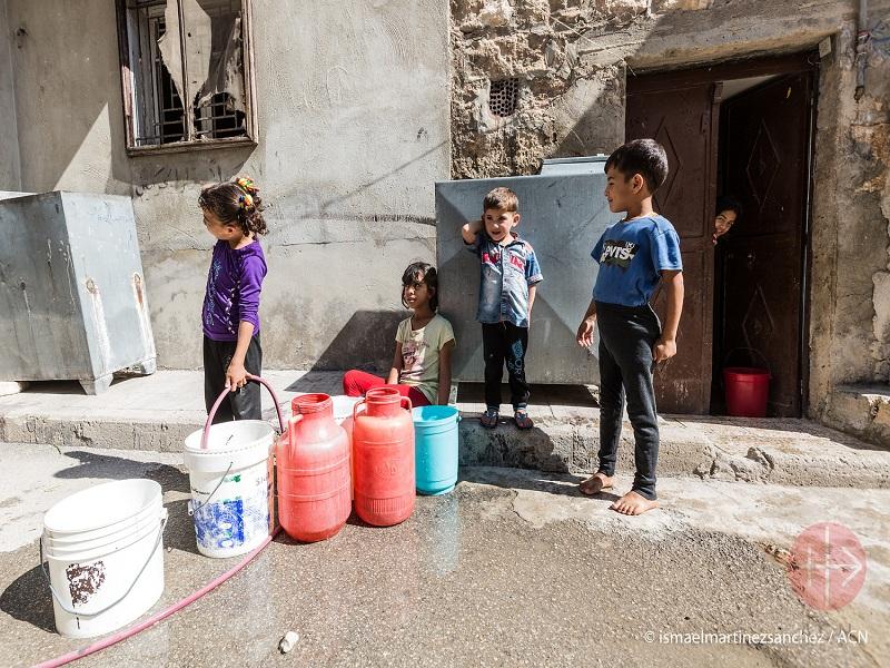 Siria niños refugiados esperan con sus bidones para llevar agua web