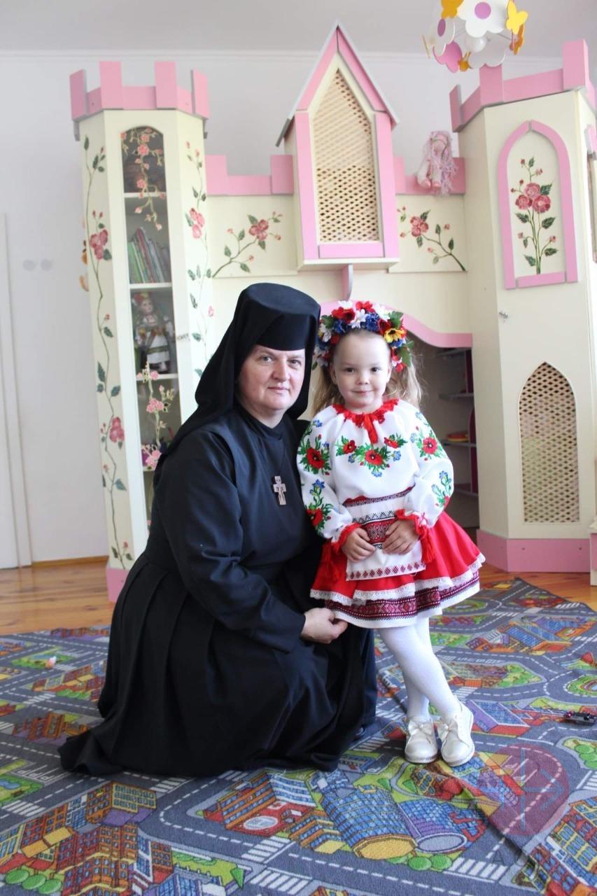Ucrania religiosa con niña en traje típico