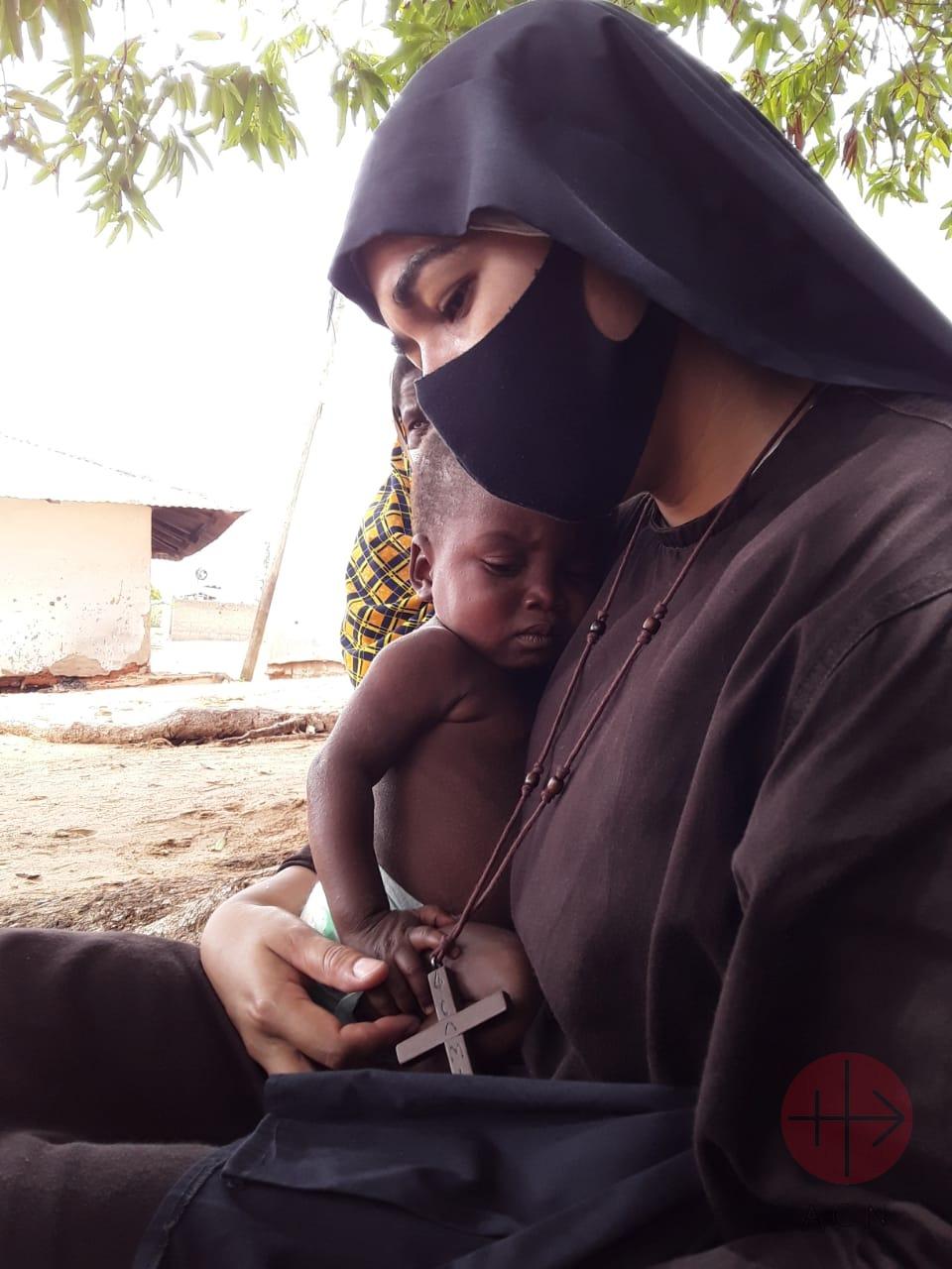 Mozambique religiosa consuela a niño pequeño