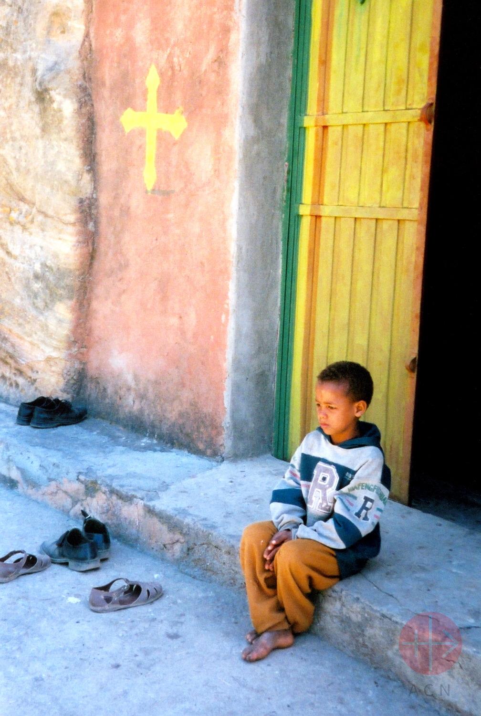 Etiopia niño en portal con una cruz copta en el muro