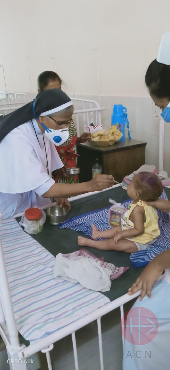India religiosa alimentando a un niño en el hospital