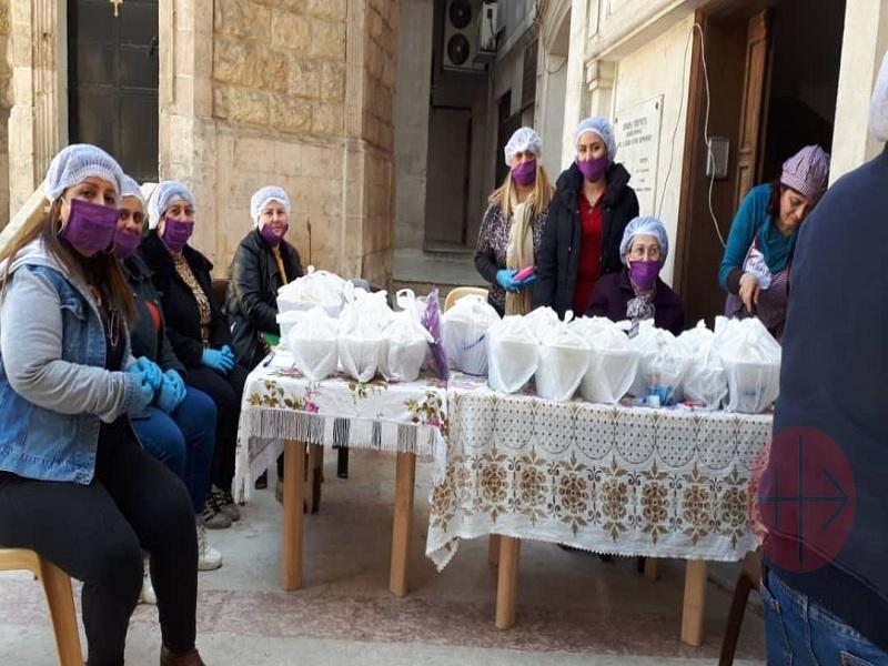 Siria mujeres frente a platos de comida para entregar web