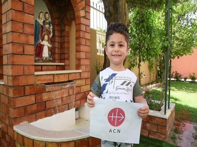 Irak niño con letrero acn en jardin infantil sagrada familia web